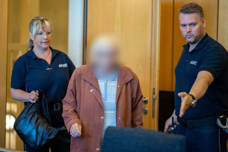 Die Angeklagte wird beim Prozessbeginn im Landgericht Münster von zwei Justizbeamten in den Saal geführt.
