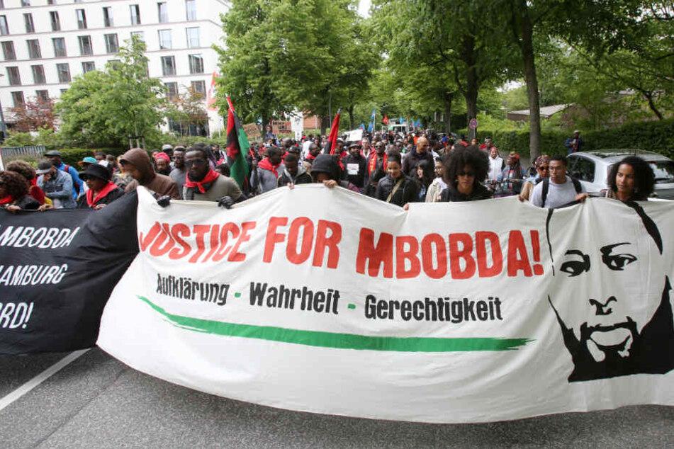 """Auf Plakaten forderten die Menschen die Aufklärung im """"Fall Mbobda""""."""