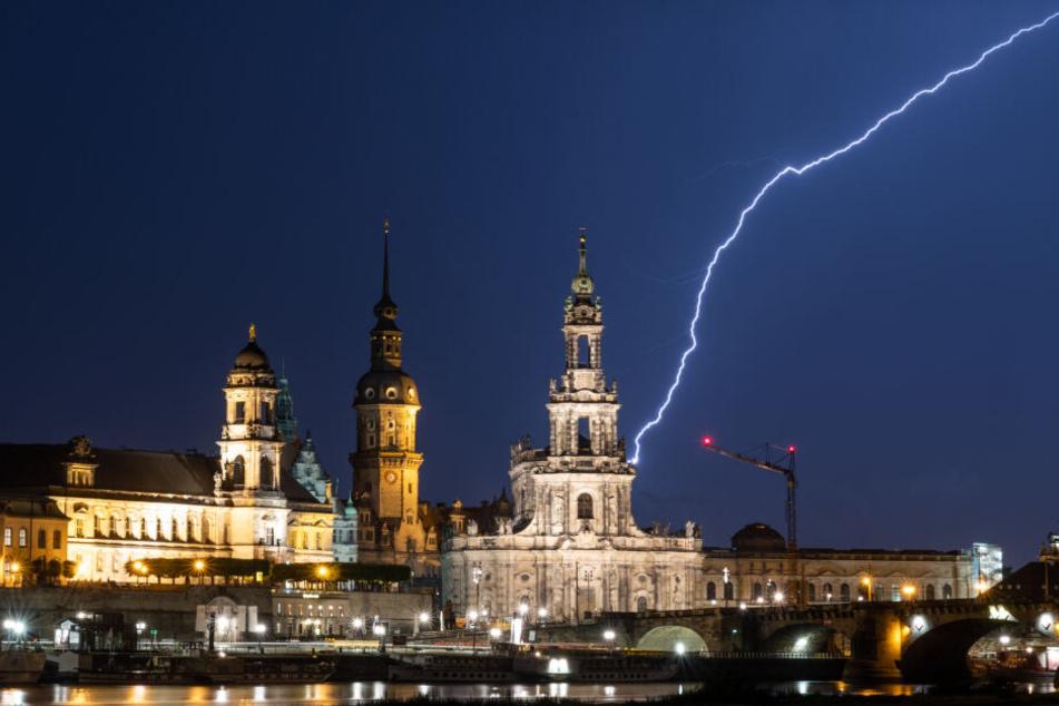 Blitze schlagen während eines Gewitters am Abend in die historische Altstadtkulisse in Dresden ein.