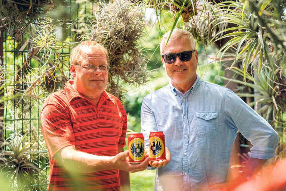 """Lieferauftrag erledigt. Jens Teichert (56, l.) nimmt von MOPO-Reporter Torsten Hilscher (51) das Bier aus Costa Rica entgegen. Die Marke """"Imperial"""" ist seine zweite große Leidenschaft neben den Bromelien, die ringsum hängen."""