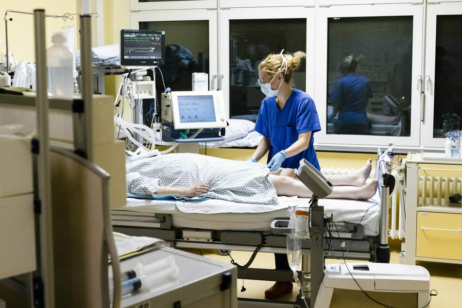 Eine Krankenschwester kümmert sich um einen Patienten auf der Intensivstation.