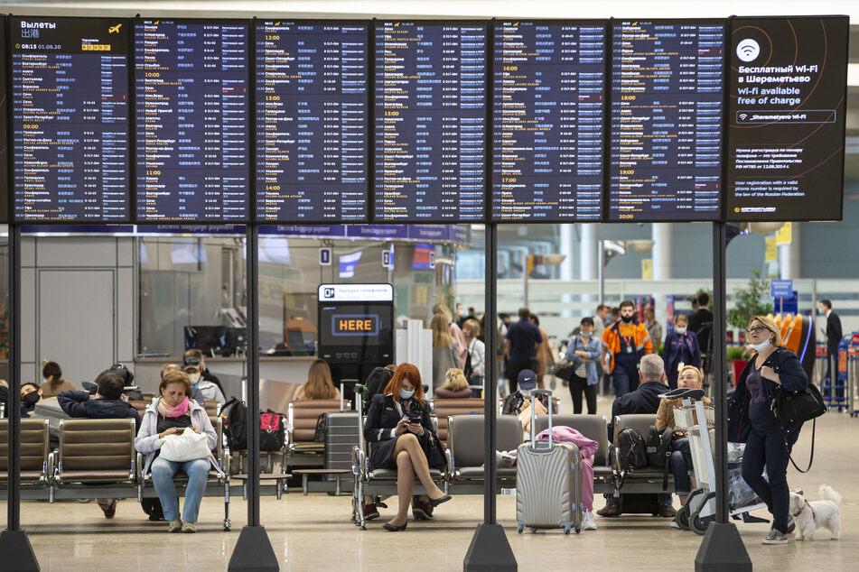 Russland, Moskau: Passagiere sitzen auf dem internationalen Flughafen Scheremetjewo unter einer Fluginformationstafel.