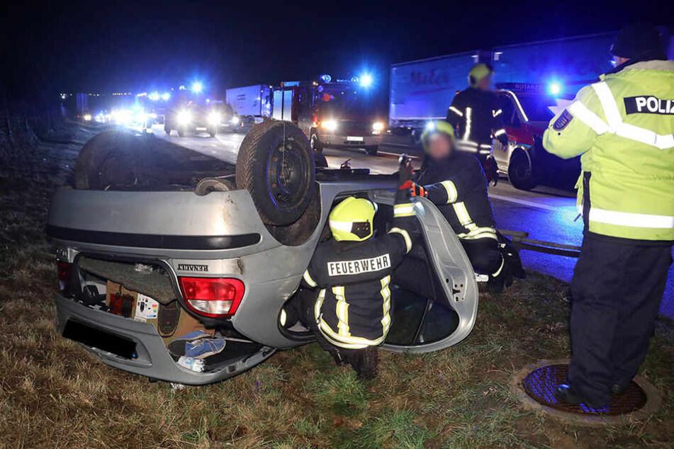 Die Feuerwehrleute sichern das verunfallte Auto.