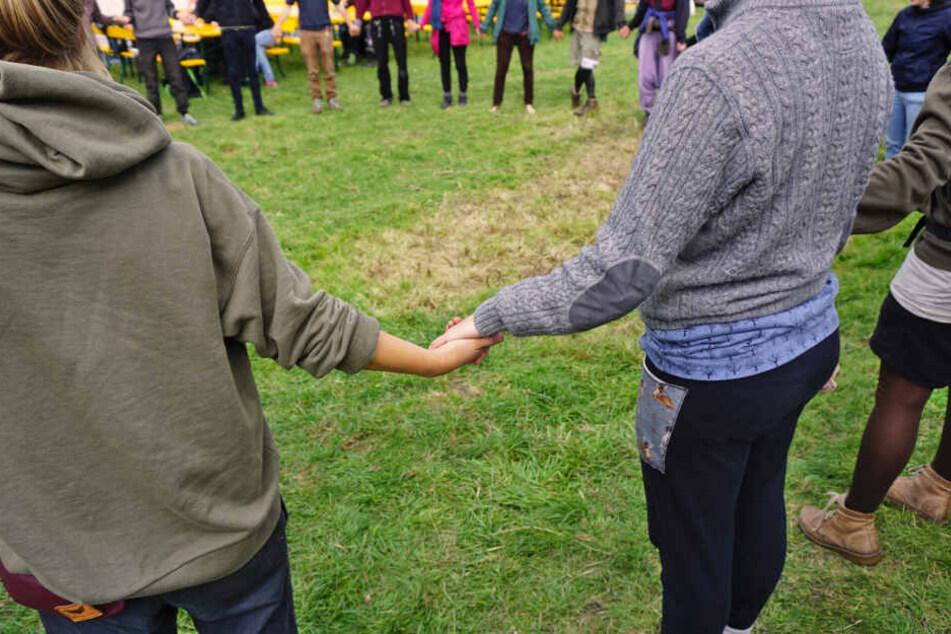 """Aktivisten der Organisation """"Free the Soil"""" halten sich an den Händen."""