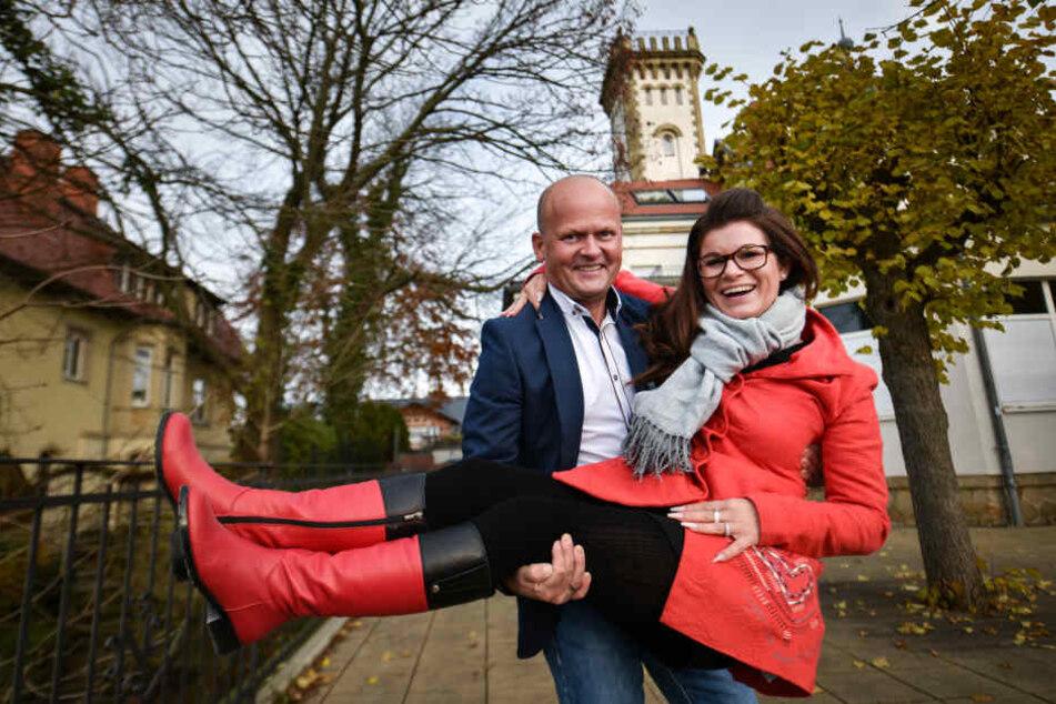 Carsten Rühle (48) trägt seine Frau Carolin (36) über die Schwelle seines künftigen Restaurants auf die Terrasse des Luisenhofs.