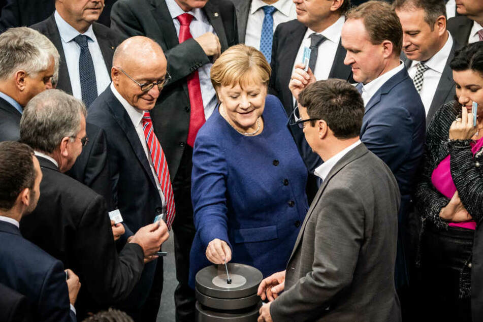 Bundeskanzlerin Angela Merkel, wirft bei der namentlichen Abstimmung zum Solidaritätszuschlag ihre Stimmkarte ein.
