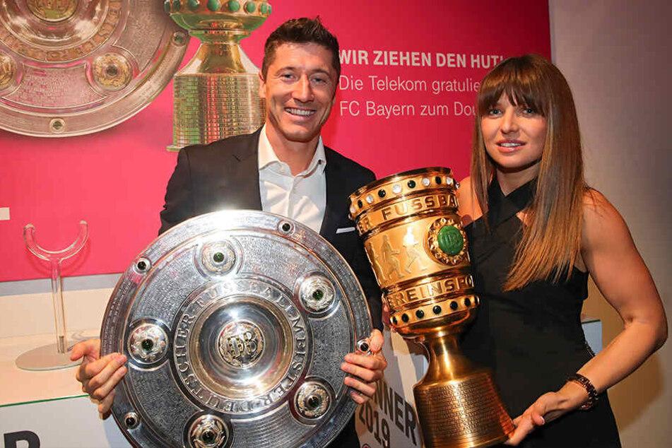 Robert Lewandowski und seine Frau Anna posieren mit DFB-Pokal und Meisterschale in der Finalnacht 2019 beim offiziellen Bankett des FC Bayern München in Berlin.