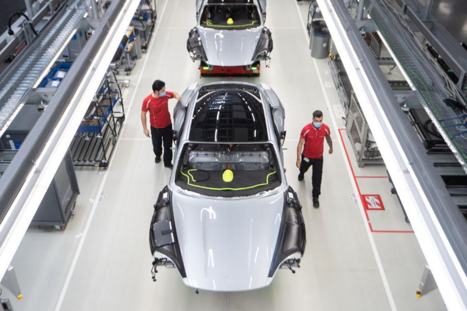 Baden-Württemberg, Stuttgart: Mitarbeiter der Porsche AG haben in der Produktion des batterieelektrisch angetriebenen Sportwagens Porsche Taycan einen Mundschutz an. Die Aufträge in der deutschen Autobranche wachsen stark.