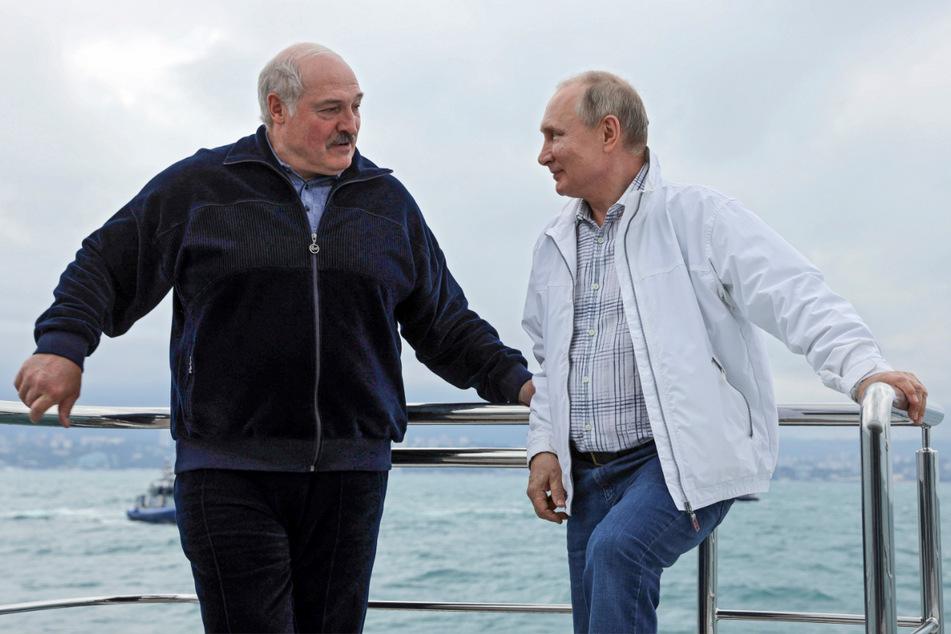 Wladimir Putin, Präsident von Russland, und Alexander Lukaschenko, Präsident von Belarus, stehen auf einem Boot und unterhalten sich miteinander während eines Treffens in Sotschi am Schwarzen Meer.
