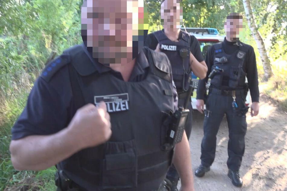 Ein weiterer Ausschnitt aus dem Video zeigt den übergriffigen Polizisten kurz nach dem Vorfall, wie er auf sein Namensschild zeigt. Im Hintergrund stehen zwei seiner Kollegen, die den Übergriff laut Stähle beobachtet haben.