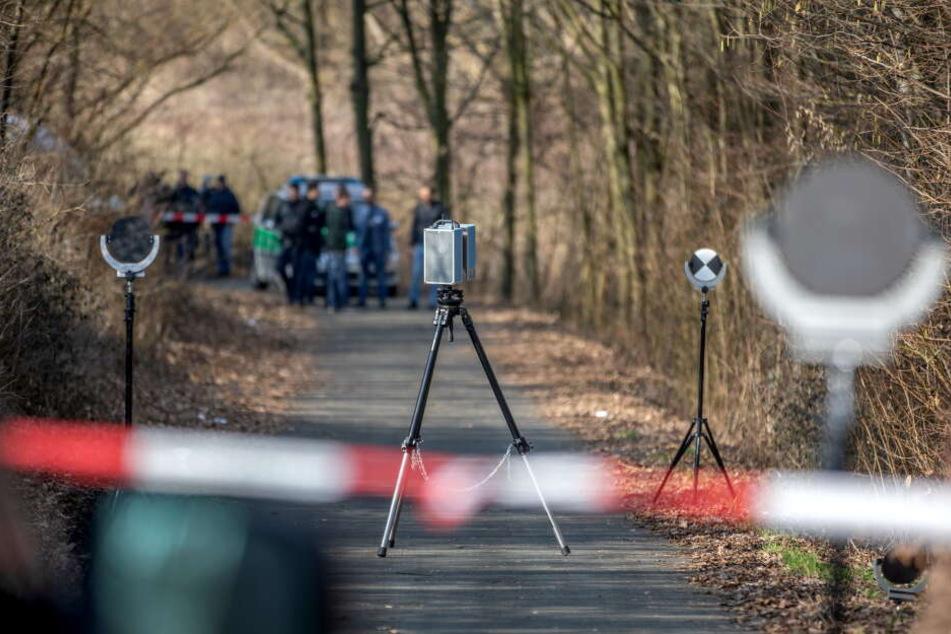 Spurensicherer der Polizei arbeiten an einer Böschung: Eine Spaziergängerin hatte dort eine Leiche gefunden.