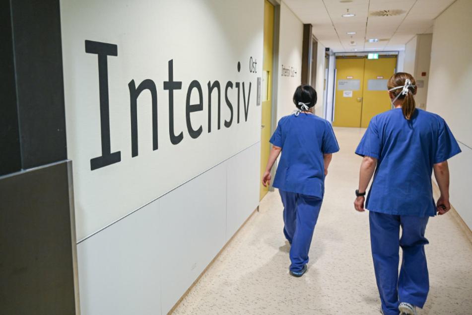 """Zwei Pflegerinnen gehen an dem Schriftzug """"Intensiv"""" vorbei."""