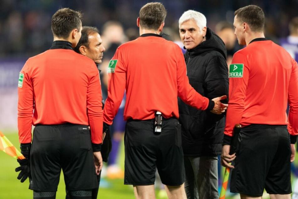 Sportdirektor Andreas Bornemann (2.v.r.) und Trainer Jos Luhukay (2.v.l.) diskutieren nach dem Spiel mit Schiedsrichter Markus Schmidt (3.v.l.) und seinen Assistenten.