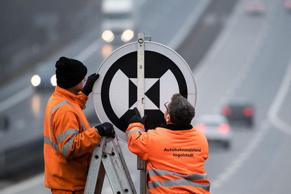 Zwei Mitarbeiter der Autobahnmeisterei stellen ein neues Verkehrsschild auf.