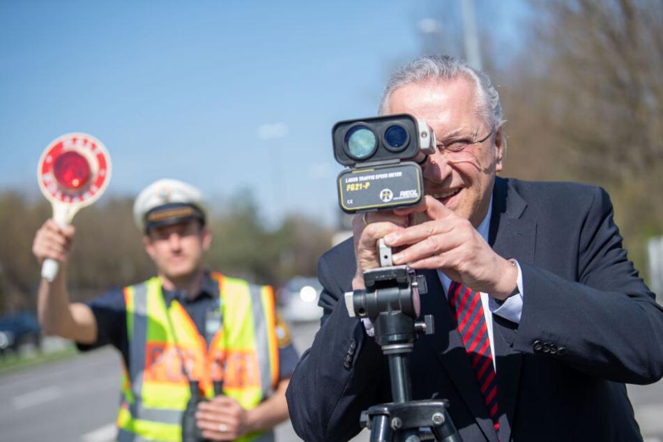 Joachim Herrmann (CSU), Innenminister von Bayern, steht bei einer Blitzmarathon-Kontrollstelle hinter einem Geschwindigkeitsmessgerät.