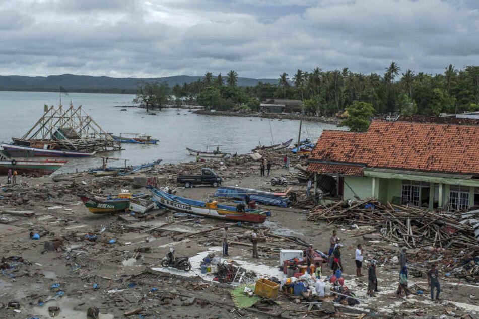 Menschen untersuchen die Schäden in einem von einem Tsunami getroffenen und verwüsteten Dorf.
