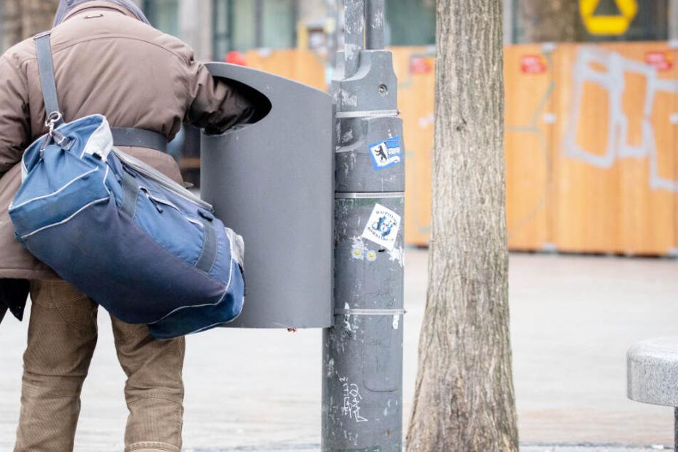 Ein Mann sucht in einem Mülleimer nach Pfandflaschen.