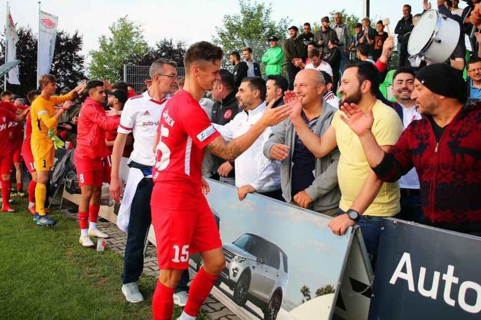 Die Spieler von Türkgücü München klatschen mit ihren Fans ab.