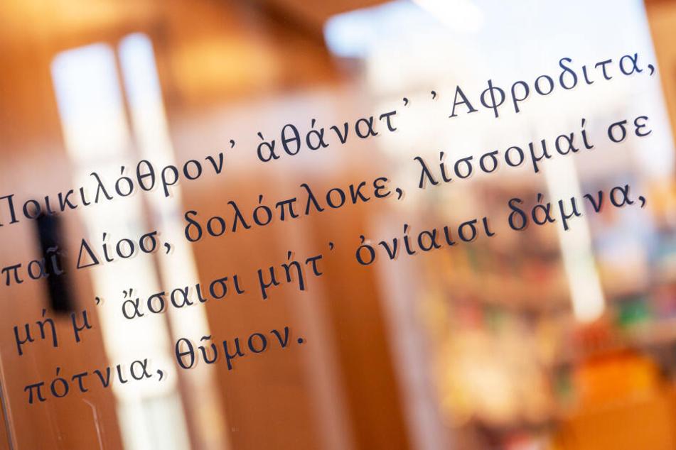 Finde den Fehler: Die in Griechisch geschriebene Textstelle der Dichterin Sappho klebt an einer großen Glasscheibe im neuen Philologicum der Ludwig-Maximilians-Universität (LMU).