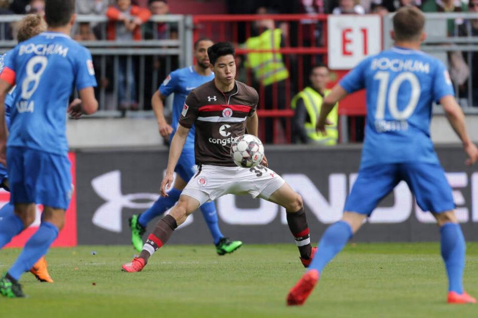 YiYoung Park schirmt den Ball vor seinen Gegenspielern ab.
