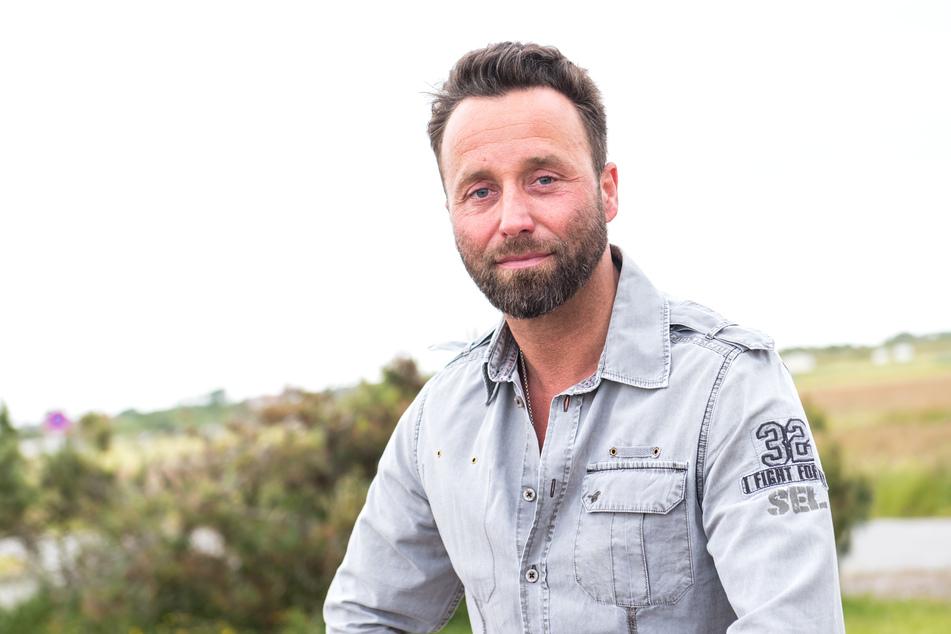 Der Sylter Dirk Lins (44) lächelt auf der Nordseeinsel im Ort Westerland. Lins unterstützt nebenbei Film- und Fernsehproduktionen als Location-Scout und sogenannter Runner auf seiner Heimatinsel.