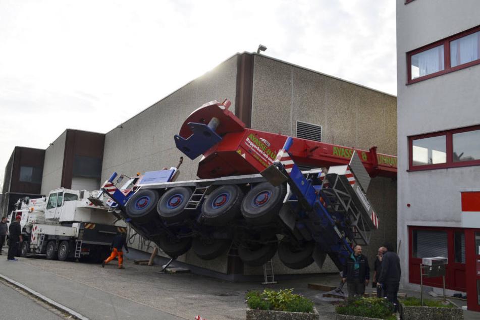 Der Fahrzeugkran wurde durch seinen Fall ungünstig zwischen den Gebäuden eingeklemmt.