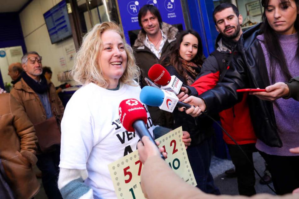 Eine Frau, die auf die Losnummer 57342 der Jesuskind-Lotterie setzte, spricht mit Journalisten.