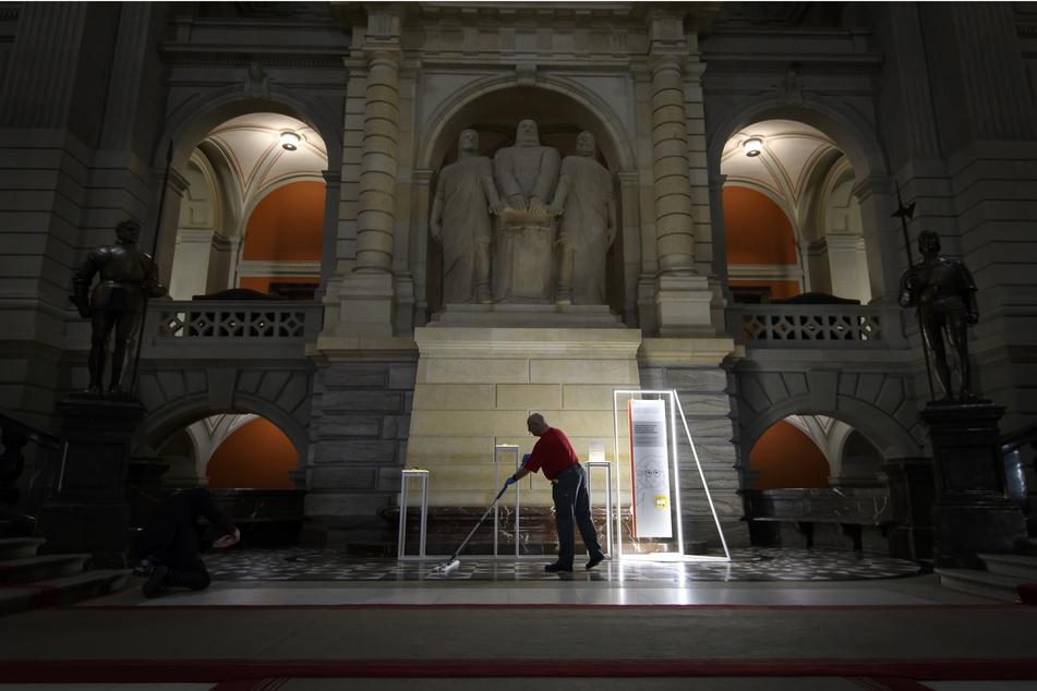 Ein Mann reinigt den Boden in der Eingangshalle des Parlamentgebäudes. Die letzte Woche der Frühlingssitzungen der Eidgenössischen Räte wird wegen COVID-19 abgesagt.