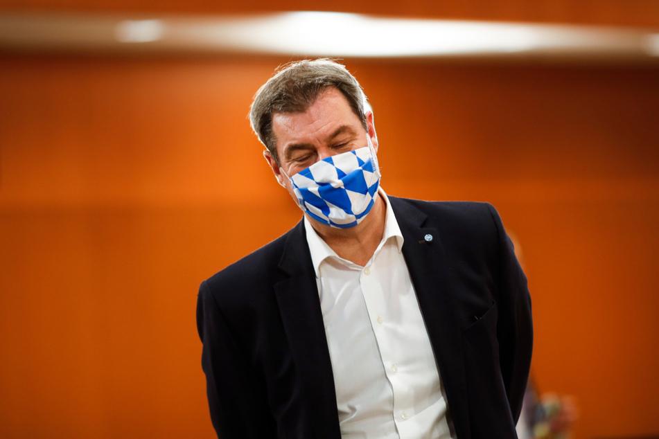Markus Söder, Ministerpräsident von Bayern, trägt eine Gesichtsmaske mit dem weiß-blauen Rautenmuster Bayerns, als er am Mittwoch zu einer Gesprächsrunde zwischen Bundeskanzlerin Merkel und Ministerpräsidenten der Bundesländer im Kanzleramt eintrifft.