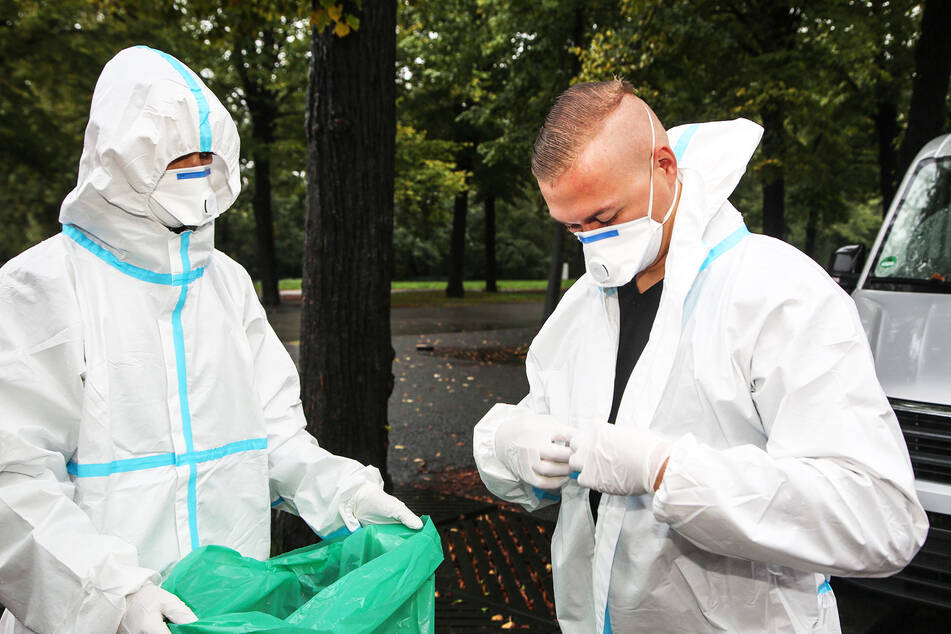 Zwei Soldaten ziehen ihre Schutzkleidung aus, nachdem sie einen Abstrich bei einer Corona-Verdachtsperson genommen haben.