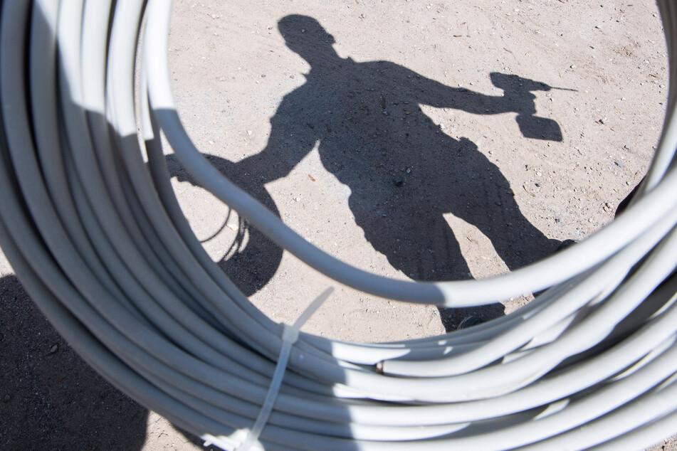 Ein Auszubildender eines Elektroinstallationsbetriebes wirft mit aufgerolltem Kabel und einem Akkuschrauber einen Schatten. Die Bundesagentur für Arbeit hat Jugendliche in Mecklenburg-Vorpommern aufgerufen, sich um einen Ausbildungsplatz zu bemühen. (Symbolbild)