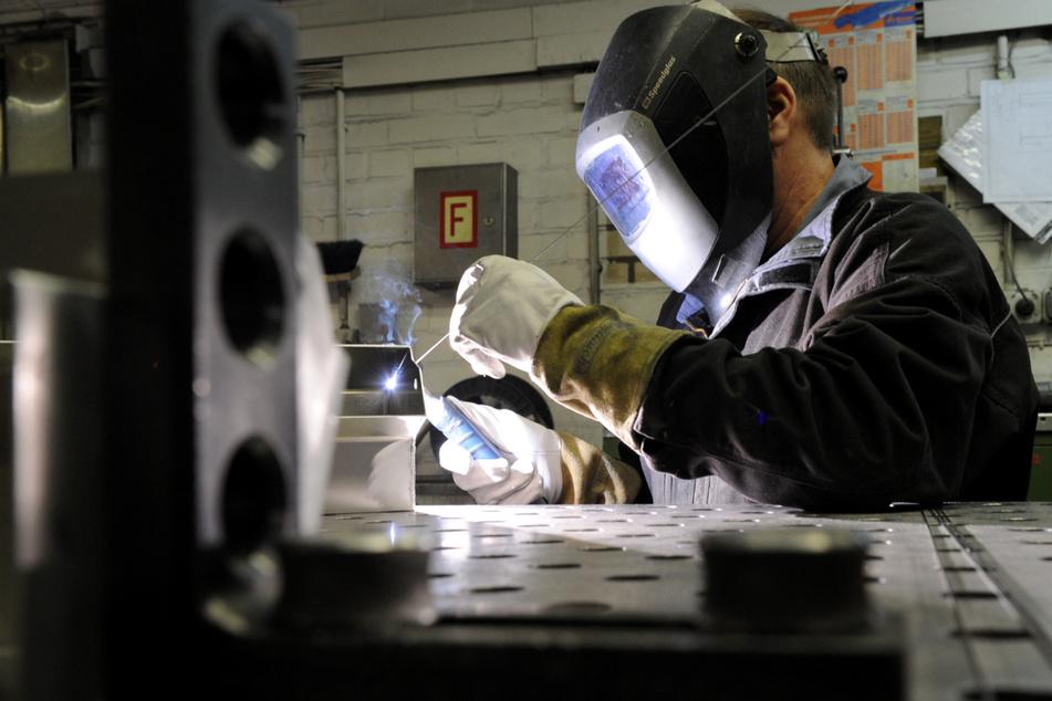 Ein Mitarbeiter eines metallverarbeitenden Betriebes schweißt eine Naht an einem Werkstück.