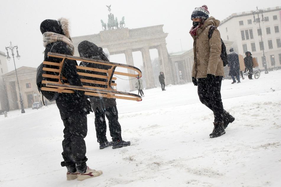 Mit einem Schlitten unter dem Arm und in dicke Jacken eingepackt, laufen italienische Touristinnen bei Schneetreiben und Temperaturen um -10 Grad Celsius über den Pariser Platz am Brandenburger Tor.