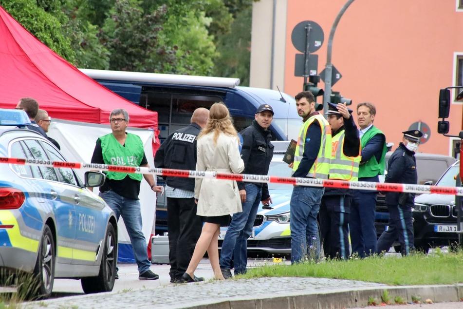 Polizisten stehen am Tatort, an dem zuvor ein Mann auf der Straße umgebracht wurde.