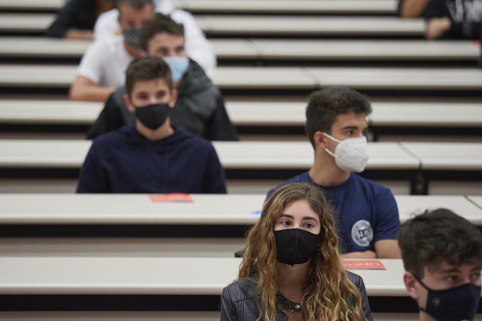 Studenten, die Mundschutz tragen, sitzen in einem Hörsaal.