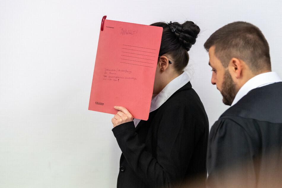 Die Angeklagte Jennifer W., die sich der Terrormiliz Islamischer Staat (IS) im Irak angeschlossen haben soll, hält sich beim Betreten des Gerichtssaals einen roten Aktendeckel vors Gesicht. Rechts steht ihr Anwalt Ali Aydin. (Archiv)