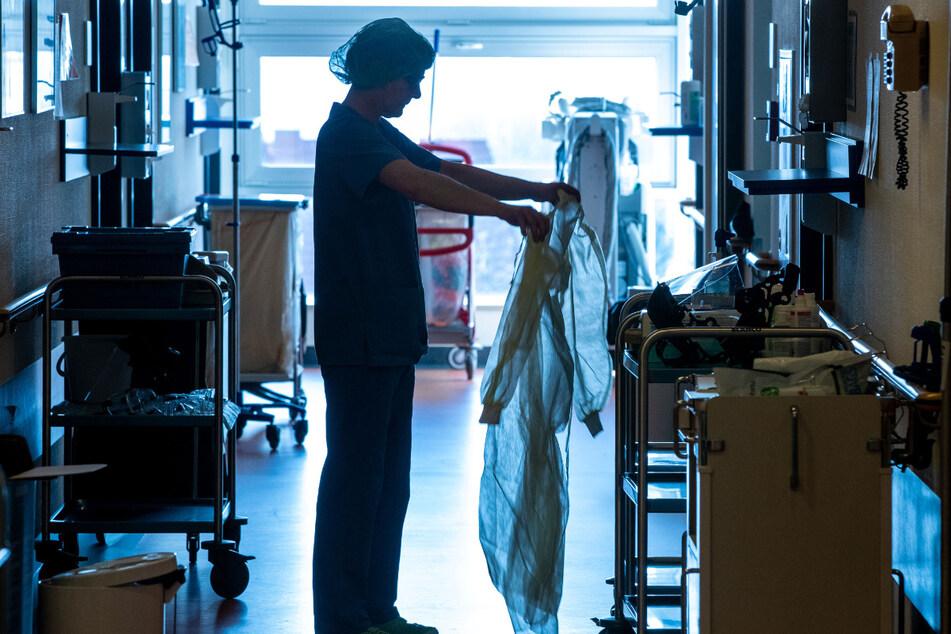 Eine Krankenschwester legt auf der Isolierstation für Coronavirus-Behandlungen einer Klinik in Mecklenburg-Vorpommern Schutzkleidung an, bevor sie ein Patientenzimmer betritt. Schutzmasken und -kittel müssten regelmäßig erneuert werden.