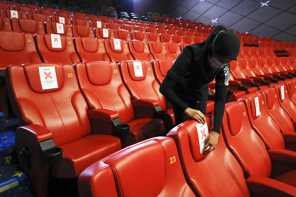 Eine Mitarbeiterin eines Kinos in Malaysia klebt Hinweiszettel zur Einhaltung des Mindestabstands an die Sessel im Kinosaal. (Symbolbild)