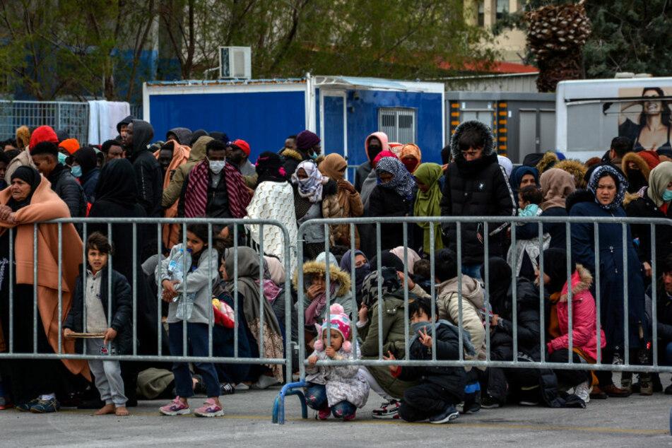 Migranten warten an einer Absperrung auf die Versorgung durch die griechischen Behörden mit Lebensmitteln.