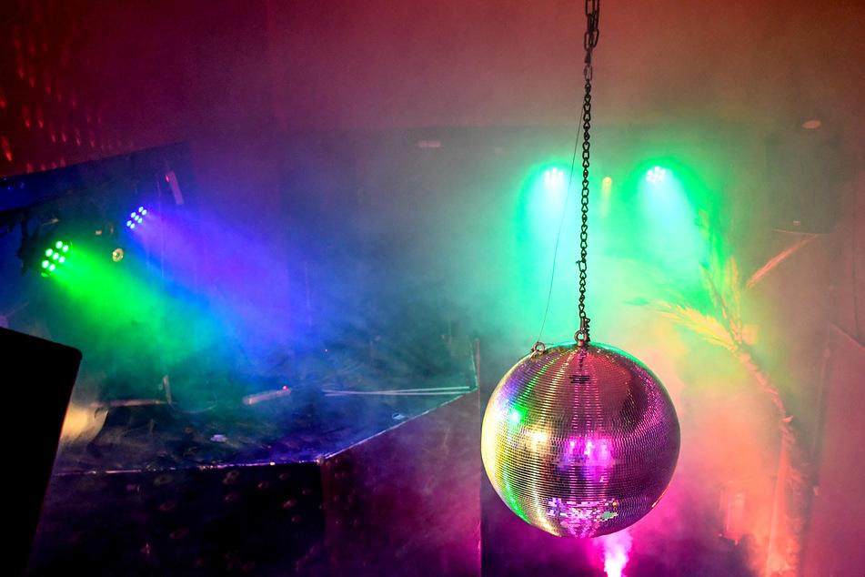 Eine Diskokugel dreht sich in einem Club und reflektiert das einfallende Licht der Scheinwerfer und Lampen. Clubs, Diskotheken, Bars - sie alle stehen in der Corona-Krise vor dem Abgrund.