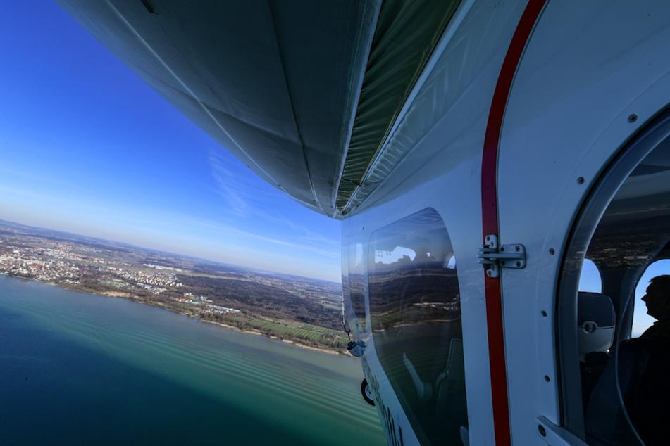 Der Zeppelin NT (Neue Technologie) fliegt über dem Bodensee, während im Hintergrund Friedrichshafen zu sehen ist.