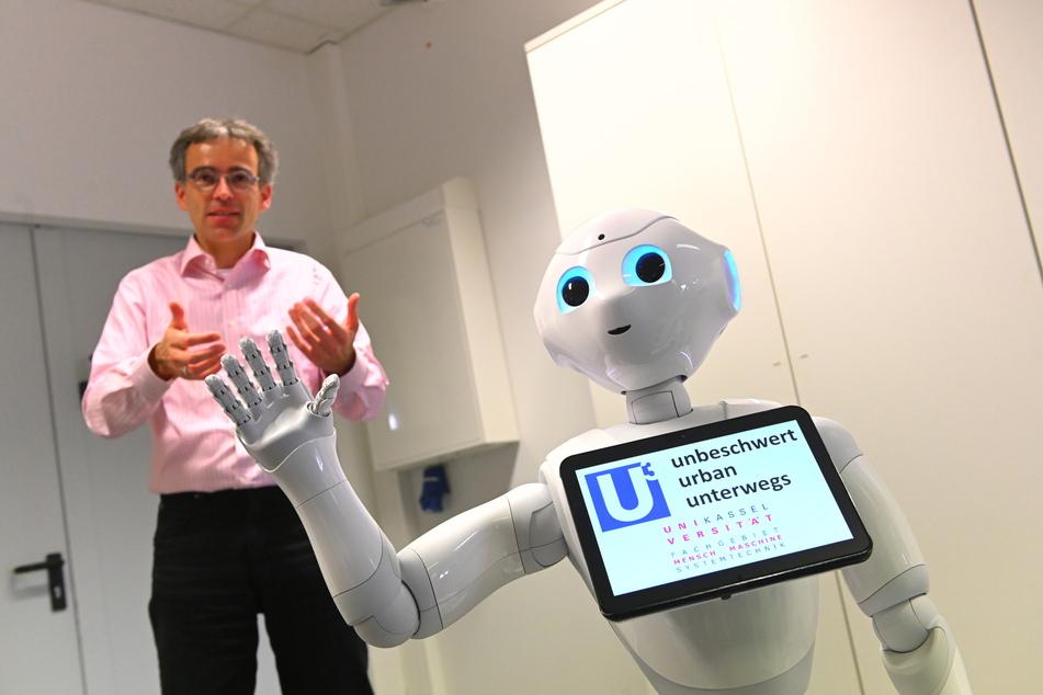"Professor Ludger Schmidt steht hinter Roboter Pepper. Der Roboter ist Teil des millionenschweren Forschungsprojekts ""Unbeschwert urban unterwegs"" (U-hoch-3)."