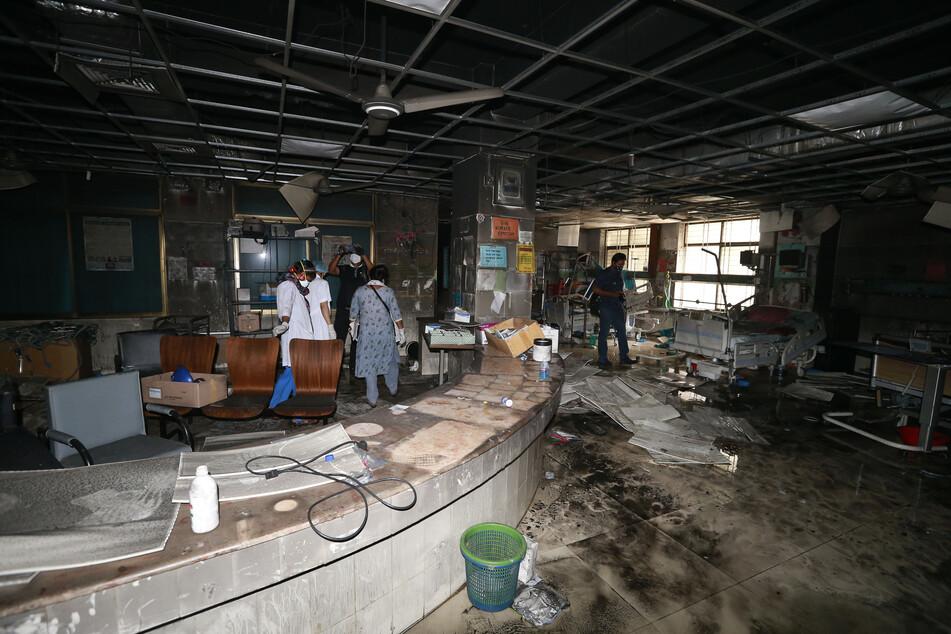 Menschen stehen in einem ausgebrannten Teil eines Krankenhauses, das bei einem Feuer beschädigt wurde.