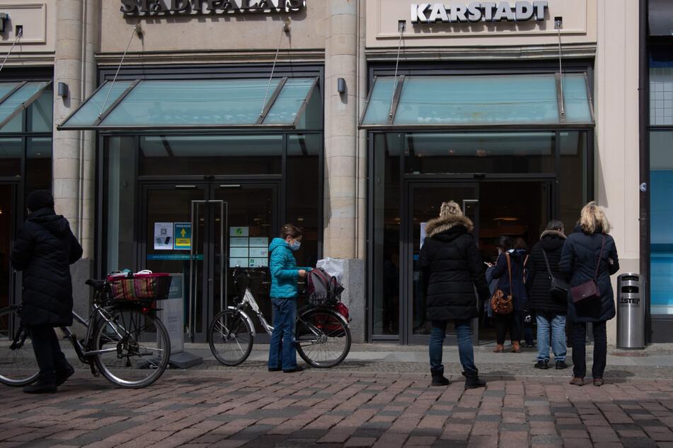 Menschen stehen in Potsdam am Eingang eines Geschäftes und warten auf Einlass. Die Zahl der Neuinfektionen mit dem Coronavirus ist in Brandenburg weiterhin hoch.