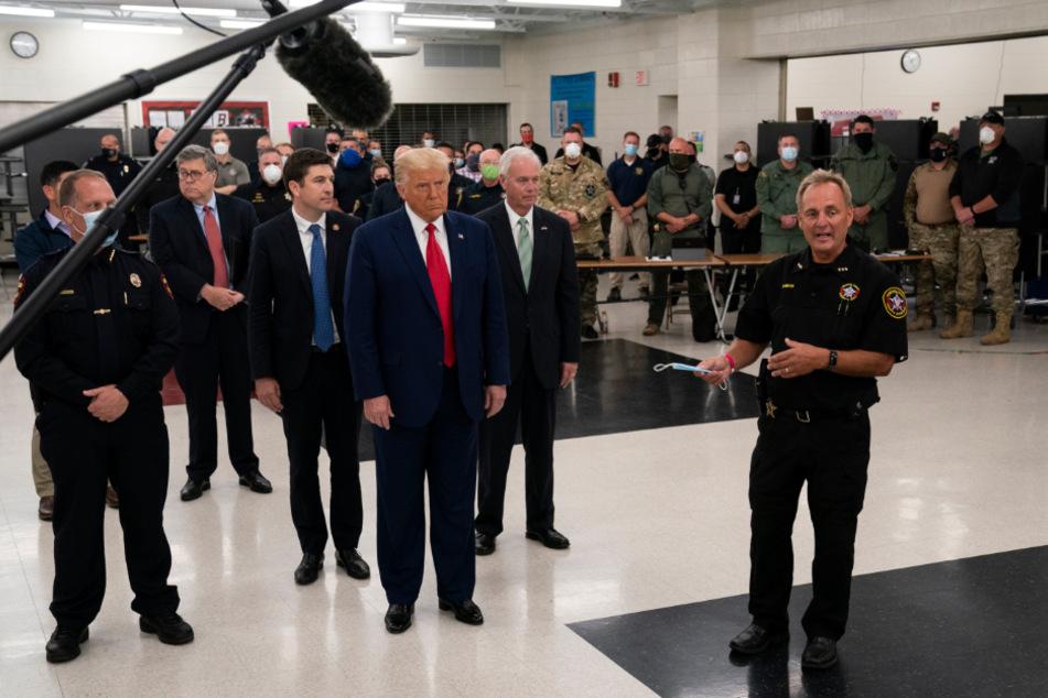 Donald Trump hört zu, während der Kenosha-Sheriff David Beth (r.) in der Notfallzentrale der Mary D. Bradford High School spricht.