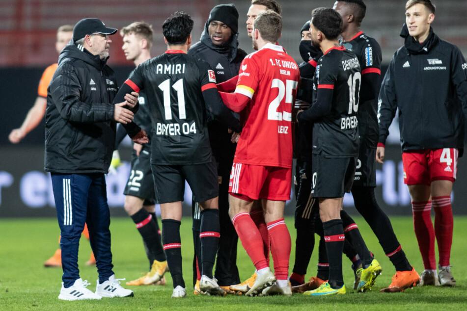 Unions Trainer Urs Fischer (54, l.) und Christopher Lenz (26, 4.v.l.) halten Nadiem Amiri (24, 2.v.l) von Bayer Leverkusen am Arm.