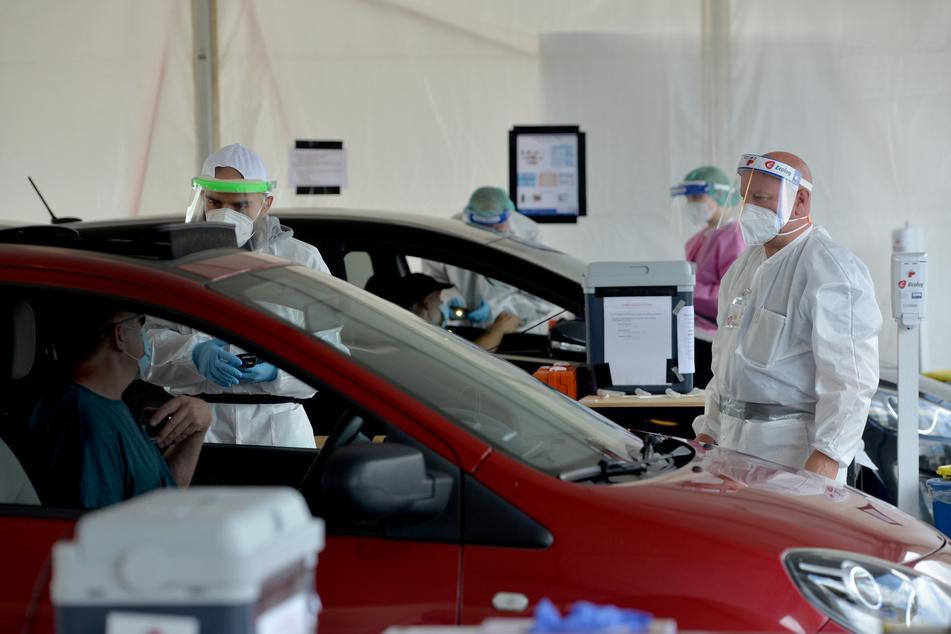 Luxemburg, Bascharage: Medizinische Mitarbeiter kümmern sich um Personen, die mit dem Fahrzeug zu einer der Stationen gekommen sind, um sich auf den Coronavirus testen zu lassen. (Archivbild)