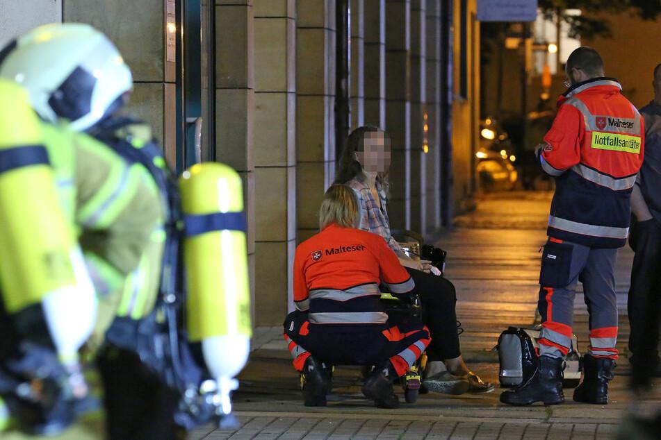 Rettungskräfte kümmern sich um eine Bewohnerin. Der Verdacht der Rauchgasvergiftung bestätigte sich bei ihr nicht.