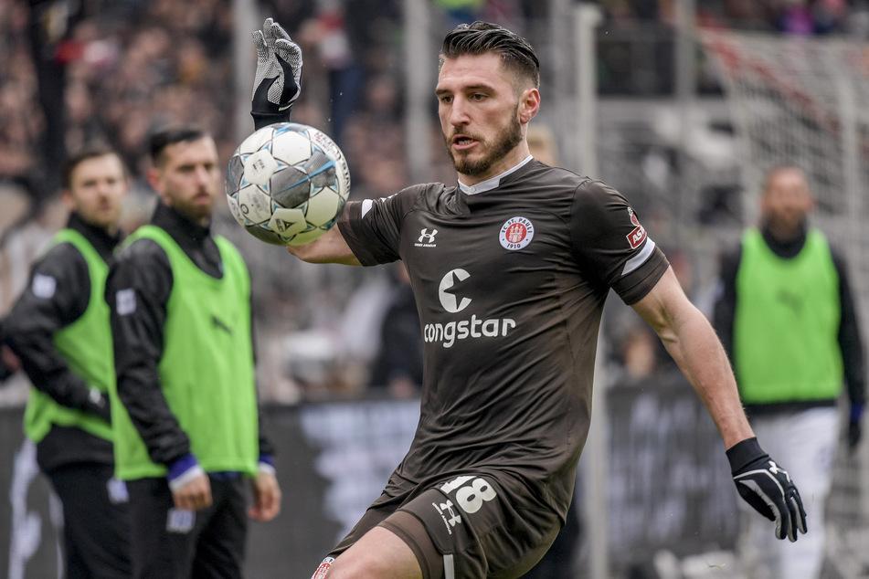 St. Paulis Dimitrios Diamantakos versucht einen Ball vor den Osnabrücker Auswechselspielern zu kontrollieren.