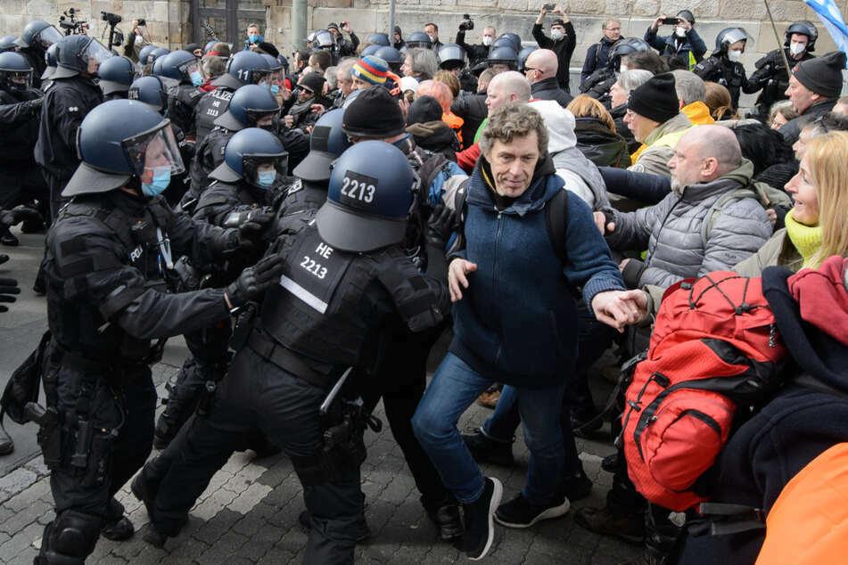 """Einsatzkräfte der Polizei halten bei einer Kundgebung unter dem Motto """"Freie Bürger Kassel - Grundrechte und Demokratie"""" Teilnehmer zurück."""
